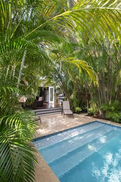 Just steps out of this historic Key West cottage is a relaxing swimming pool surrounded by gorgeous palms for an oasis-like backyard. The deck features dark, glossy wood and comfortable wicker furniture, creating a family-friendly outdoor living space.