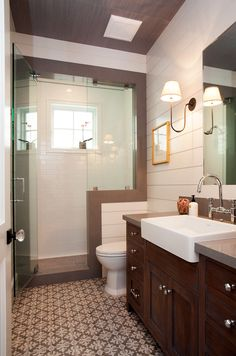 This first floor bathroom brings the style with its gorgeous mix of materials. Contemporary meets traditional with the combination of white shiplap walls, caesarstone pebble quartz counter top and shower jamb, and hand crafted vanity with custom stain applied.
