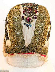 NEWBORN'S EMBROIDERED CAP, EUROPE, 18TH C White silk edged in gold gilt lace w/ embroidered gold sequins, stamped colored sequins & gold bullion, lace edging, pink & white cotton lining,