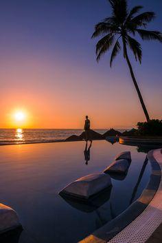 Invitation - Infinity pool and woman at sunset, Puerto Vallarta, Mexico.