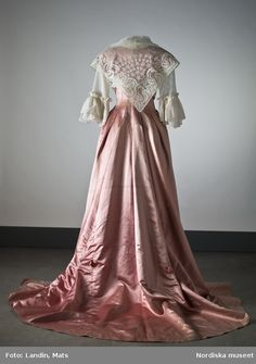 Back view of 1780s gown of pink atlas with fichu and chemise and elbow length sleeves ending in flounce, Sweden. Via Nordiska museet.