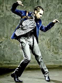 Wade Jeremy William Robson is an Australian dancer and choreographer. Twist ~ he is in front of a wall, the wall has similar green tones and his body is curved to one side.