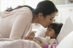 Asian mother comforting daughter in bed.