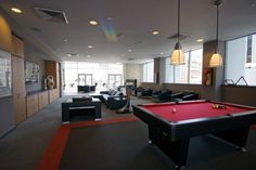 This photo shows individual industrial style pendant lights with single individual canapies over the pool table.  Note the furniture layout in front of TV viewing area.  Similarly, we have a sectional that starts on the far right side and turns to the left with a lot of area behind it for additional seating.  Perhaps, a round table and chairs as shown in the foreground of this photo would be appropriate.  Or, the poker table and chairs could be placed there and the poker table room could be…