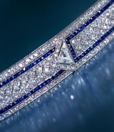 An art deco diamond and sapphire bracelet, Oscar Heyman & Brothers, circa 1923. Of geometric design, set throughout with transitional and square step cut-diamonds, with French-cut sapphire detail; centering three triangular-cut diamonds, weighing 2.87 carats total; with maker's mark for Oscar Heyman & Brothers; no. 10517; estimated remaining total diamond weight: 24.60 carats; mounted in platinum; length: 7 1/8in. Via Bonhams.
