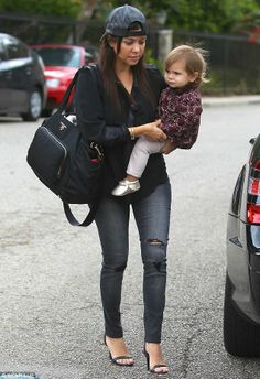 Casual chic: Kourtney Kardashian rocked a casual outfit of jeans and a shirt but jazzed it up with stiletto sandals and with her daughter Penelope Disick