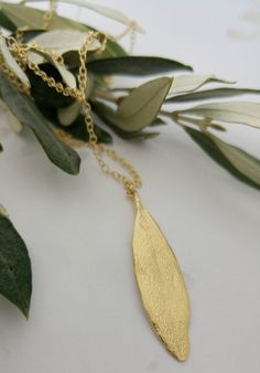 This gold necklace olive leaf pendant and chain,are an exact replica of an ancient olive tree leaf. made of 18k gold plated.  stand alone or paired with matching earrings, this piece has a special Judaic meaning, the olive being one of the blessed seven species.  Real leaf necklace from my Natural Collection  Free shipping from Israel included  DIMENSIONS:  length of chain without pendant - 49cm/19 Length of pendant - 4.6cm/1.9.   All jewelry is hand made at my home studio using traditional…