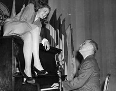 Actress Lauren Bacall sits atop the piano while Vice President Harry S. Truman plays at the National Press Club Canteen. They are at the canteen to entertain American servicemen, February 10, 1945.