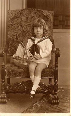 Little boy on a chair with a sailing boat in a sailor suit.