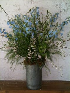 milk churn arrangment delphiniums and blossom  www.google.co.uk