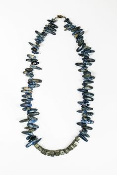 Robinhood Road Necklace  This natural blue sodalite tusk stone necklace features 11 raw unpolished pyrite beads in the center and has an antique brass button clasp. The necklace hangs near the collarbone.  Perfect to wear on its own or layered with one of my long pyrite necklaces.