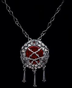 Arts & Crafts silver pendant set with a central red enamel plaque which is overlaid with flowering rose branches. Omar Ramsden; English circa 1910.