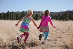 A documentary photograph of two sisters running in a field during their lifestyle family photo session in Boston, Massachusetts - Gina Brocker Photography