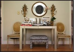 Love the ottoman below the table. And the symmetrical wall decor above, flanked by classic style chairs.