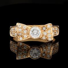 14Kt Yellow Gold Bow Ring Features One Bezel Set 0.30ct Diamond, approximately G in color and VS clarity.  The face of the ring is enhanced with an additional 24 round cut diamonds for another 0.30cts.  The ring is a size 6.0 and measures between 7mm-3mm in width.  Total weight is 3.9 grams.