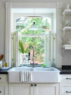Lovely kitchen with farmhouse sink, white kitchen cabinets with Absolute Black Granite countertops and white shutters.