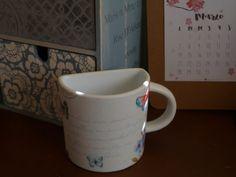 Taza de loza blanca decorada con decoupage.