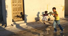 Nablus, West Bank: A Palestinian boy runs with a toy gun as children celebrate Eid al-Fitr in the Askar refugee camp