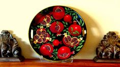 A mantle piece: large ceramic tray depicting pomegranate boughs on a black ground painted by artist Geoff Graham of Cinnabar Ceramics in Vallejo, California