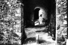 short moment - A small mountain village in Tuscany / Italy. A young man goes through an alley. The old buildings typical of Tuscany look like a tunnel. Impressionistic black and white street photography. #photography #street #streetphotography #impressionist #fineart #blackandwhite