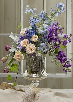 A graceful collection of garden-inspired blossoms flows freely with its modern styling, yet the arrangement is reminiscent of an old master's painting. Roses, tulips, stocks, Delphiniums, Queen Anne's lace, dusty miller, and ivy.