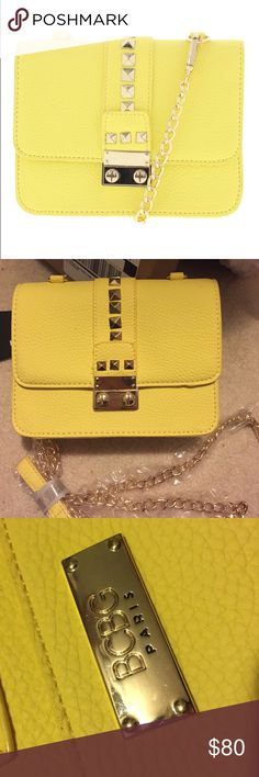 BCBG Paris Designer Handbag Brand new with tags! Fun spring-summer yellow color with gold accents. Comes with adjustable gold handles still in the wrapping. Main clasp on the front is very secure with push and slide button. Has two pockets on the inside, one includes an inside zipper. On the back of the purse contains the BCBG Paris logo. Make an offer or bundle with my other listings to save 10%! BCBG Bags Crossbody Bags
