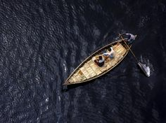"""Seen from above, a small boat travels the Buriganga River, thick and dark with pollution, in Dhaka, the capital city of Bangladesh. Though the water is filled with human and industrial waste, millions depend on it for their livelihood and transportation. """"The Buriganga is economically very important to Dhaka,"""" Your Shot photographer Jakir Hossain Rana writes. """"Launches and country boats provide a connection to other parts of Bangladesh."""""""