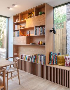 A tall bookshelf next to a window bench provides a place to display decor and a book collection. Office Interior Design, Office Interiors, Retail Interior, Interior Ideas, Oak Bookshelves, Bookshelf Built In, Plywood Shelves, Muebles Living, Built In Furniture