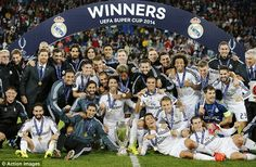 Just getting started: Real Madrid players pose with the UEFA European Super Cup trophy on the pitch.