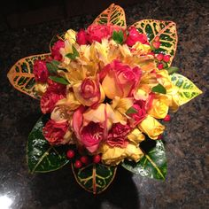 Wildrose Floral Design Wedding Collection. Autumn inspired Bridal Bouquet - Hand tied (top view) lovely rose, amaryllis & spray rose medium bouquet in shades of coral and yellow. The additional croton leaf collar is spectacular. Prices vary based on flower selection and size. Contact at wildrosefloraldesign.net or check it out on Facebook.