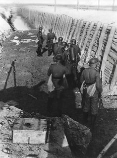 German soldiers walk the length of an anti-tank ditch at an undisclosed location, Eastern Front, 1941. Note one of the soldiers in the foreground carrying a flamethrower. They all wear the leather collar on their helmets used to hold the camouflage cover in place.