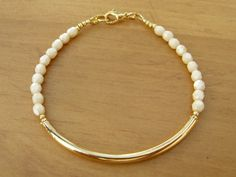 Champagne and Gold Bangle Bracelet, Beaded Friendship Bracelet, Minimalist Bracelet, Bridesmaid Bracelet, Gold Tube Bracelet, Mothers Day Gift  This beautiful gold tube bracelet features a gold plated tube bead surrounded by opaque champagne faceted glass beads. Its finished with a gold plated lobster clasp.  Looks great alone or stacked with other bracelets.  Please choose a size from the drop down menu. Default size is 6-3/4.  You will receive the bracelet in a cotton-filled gift box tied…