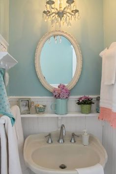 A small shelf for soaps etc. And a chandelier? Hung between the 2 mirrors? Perhaps a matching sconce on each side?
