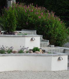 Låga svängda stödmurar av lecablock  med toppsten av betong- Design by Bonander Garden Design