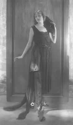 Actress Jeanne Eagels wearing a dress in black Georgette crepe, by Cheruit, with six trains and stripes of beads, with black shoes with jeweled buckles, holding an ostrich feather .