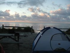 Long Key State Park!     At dawn, a tent and picnic table sit on the sand facing the ocean. Fluffy clouds spread across a blue sky over a calm sea.