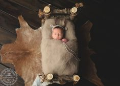 Newborn on log bed with deer bonnet and fur pelt. Portrait Pretty Photography is a baby photographer servicing all of WNY in-studio or on-location for posed or lifestyle offering Newborn Photography Buffalo