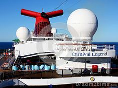 Closeup image of deck of Carnival Legend with passengers relaxing in deck chairs, bright red funnel and white radar domes, background of blue Pacific Ocean and cloudless sky.