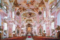 En la imatge es veu que es una església antiga pintada amb colors clars.