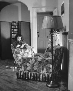 A woman reading a book in front of a fireplace, 1942. ©John Phillips