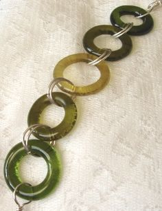 Wine bottle bracelet. The necks of the wine bottles were cut into rings & fire polished in the kiln to smooth the edges. Sterling silver jumprings and clasps are made for each bracelet.