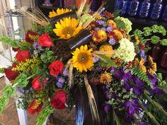 Sunflowers, red roses, purple gladiolus, mini green hydrangeas, bells of Ireland, ti leaves & wheat fall casket spray by Donna Jeffries