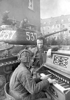 Russian soldiers playing a pump organ in war torn streets next to their tank. #WW2
