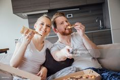 Stock Photo : Young couple watching TV and eating pizza