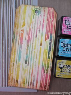 """By Britney Cheney. Ink through a stencil. Britney used picked raspberry, peacock feather, and mustard seed with the Tim Holtz """"Stripes"""" stencil. Look at this post for other results of playing with Distress Ink and stencils."""