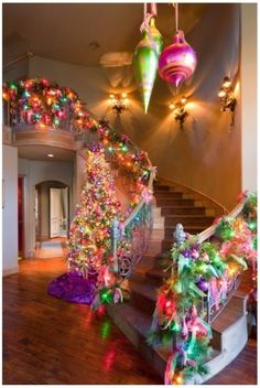 Banister with colored lights and a tree in the foyer.