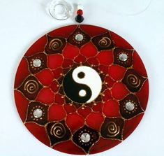 Mandala em acrílico de 12cm de diâmetro, decorada com pedrinhas vermelhas acrílicas e tinta relevo dourada.     Yin Yang  Simbolizam duas forças complementares que compõem tudo que existe, e do equilíbrio dinâmico entre elas surge todo movimento e mutação. Essas forças são:   Yang: o princípio at...