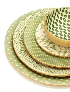 The fully handcrafted Citrus place setting includes 4 stoneware plates and one bowl. Citrus Lime and Ivory colors create intricate patterns, from nature-inspired to abstract, on the porcelain surface of each piece. The set includes:  Charger plate - in Rain pattern Dinner plate - in Braid Salad plate - in Tulle Dessert plate - in Fern Soup bowl - in Dot. Available at ArtisanCraftedHome.com