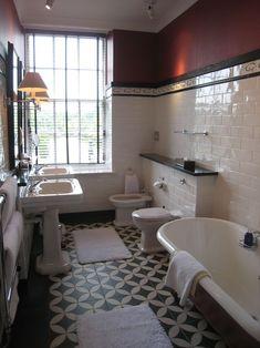 Salle de bain retro, carreaux de ciment noir et blanc à motifs, lavabo et baignoire sur pieds.