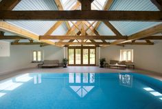 A luxurious indoor swimming pool and sauna facility for a private client in Hampshire, offers a large pool for swimming with a glazed roof to offer natural light to flood into the swimming pool. The bright blue mosaic tiles offer a stunning effect when finished against the pale stone surround and wooden beams throughout the purpose-built building.